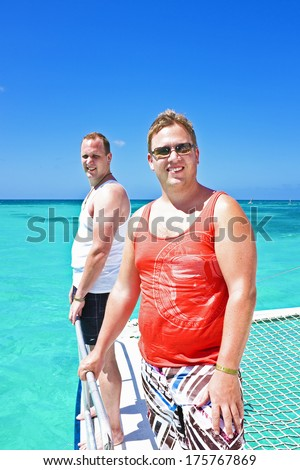 Guys sailing on a catamaran in the blue caribbean sea - stock photo