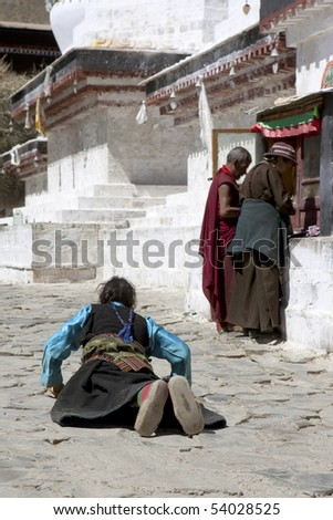 GYANTSE - CIRCA APRIL 2010: A devoted Buddhist pilgrim prostrates near a stupa at Tashilhunpo Monastery circa April 2010 in Gyantse, Tibet Autonomous Region of China.