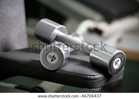 Gym apparatus and shiny chrome dumbbell - stock photo