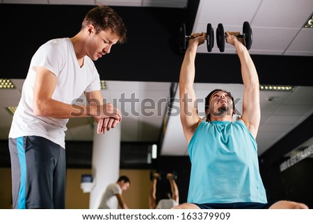 Gym buddies working out in gym timing exercise - stock photo