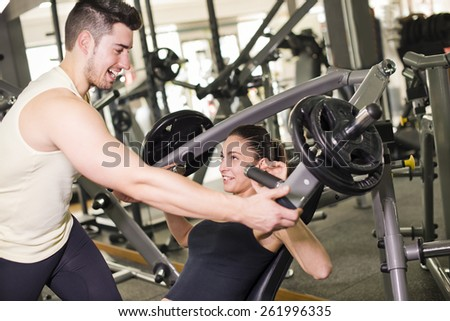 Gym coach helping girl doing pectoral exercises with ambient lightning (focus in girl)