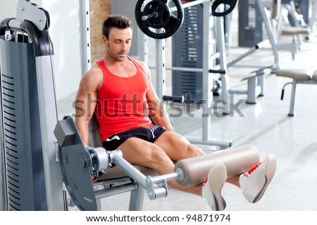 Gym fitness club indoor with young man training weights with legs - stock photo