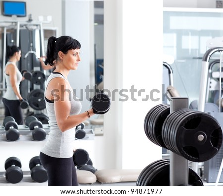 Gym fitness club indoor with young woman training weights on mirror