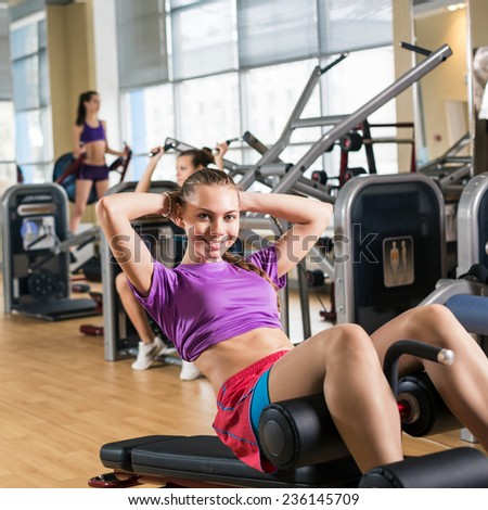 Gym fitness club indoor with young women training her abdominals - stock photo
