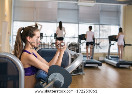 Gym fitness club indoor with young women training weights with hands