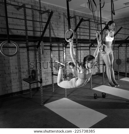 Gym girls muscle ups rings swinging workout at gym