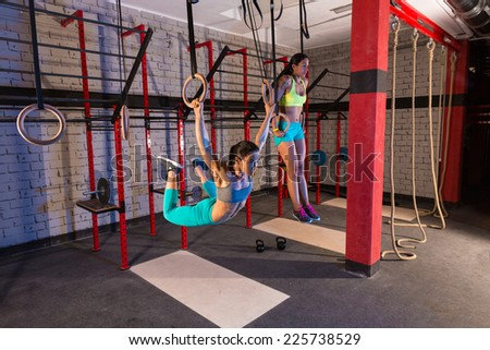 Gym girls muscle ups rings swinging workout at gym - stock photo