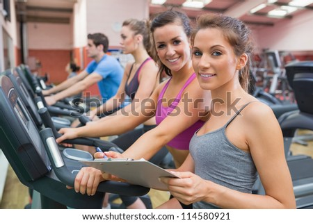 Gym Instructor and woman in the gym smiling on the exercise bicycle