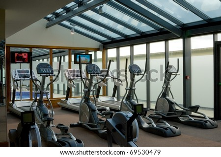 gym interior with equipment and row of jogging simulators