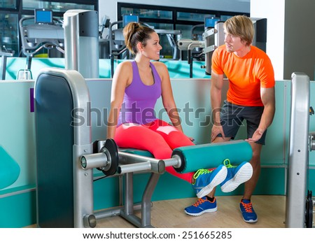 Gym leg extension exercise workout woman with blond personal trainer man - stock photo