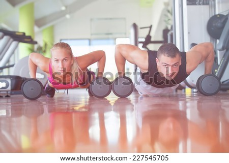 Gym man and woman push-up strength pushup with dumbbell in a fitness  - stock photo