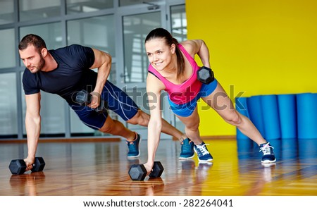 Gym man and woman push-up strength pushup with dumbbell in a fitness workout - stock photo