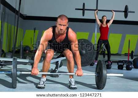 gym man and woman with weight lifting bar workout in exercise - stock photo