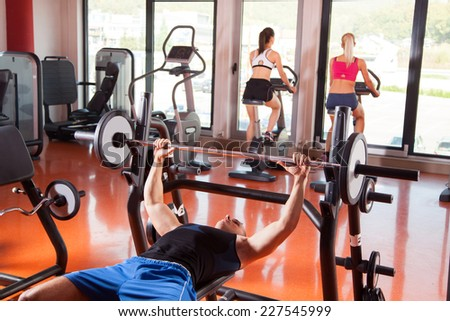 Gym man push-up strength pushup exercise with dumbbell in a fitness  - stock photo