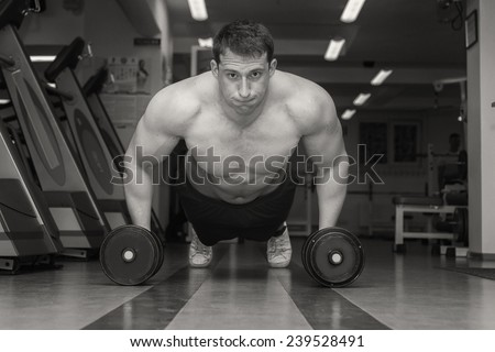 Gym man push-up strength pushup exercise with dumbbell in a fitness workout - stock photo