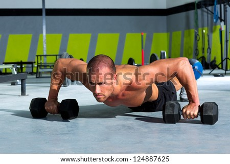 Gym man push-up strength pushup exercise with dumbbell in a workout - stock photo