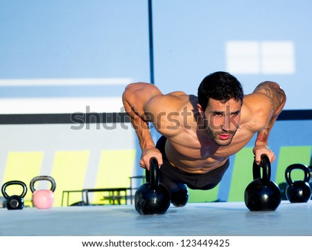 Gym man push-up strength pushup exercise with Kettlebell in a workout - stock photo