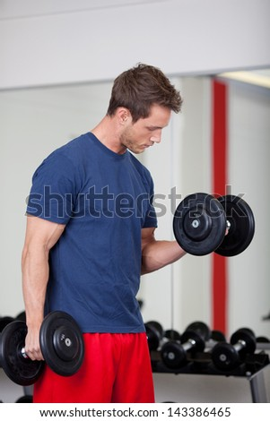 Gym man with dumbbells weights lifting exercise cross fit fitness workout