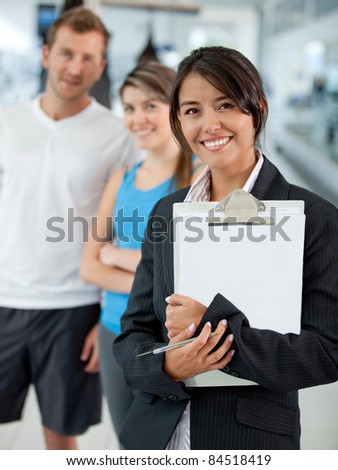 Gym manager showing the facilities to a couple - stock photo