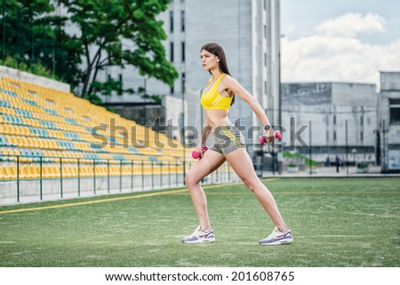 Gym Outdoors. Young woman doing fitness training on the football field on the street - stock photo