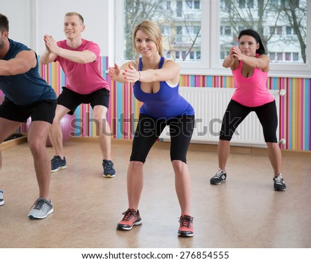 Gym people doing squats during fitness classes - stock photo