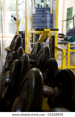 gym with machines and iron weights - stock photo