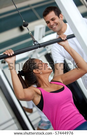 gym woman and her trainer doing exercise at the gym - stock photo
