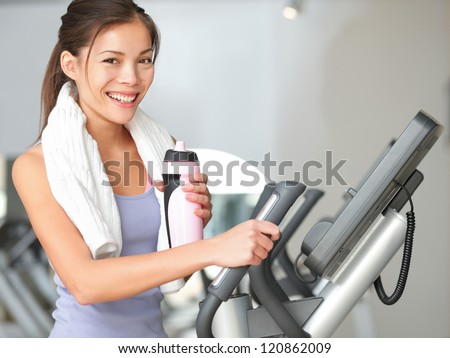 Gym woman fitness workout. Fitness girl exercising on moonwalker treadmill gym equipment. Young mixed-race Caucasian / Asian Chinese fitness model looking at camera smiling.