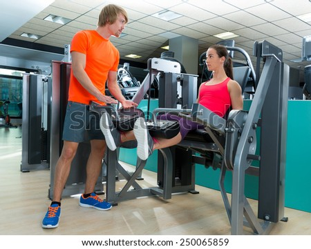 Gym woman leg extension cuadriceps exercise workout with personal trainer - stock photo