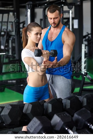 gym woman personal trainer man with weight training equipment in modern gym