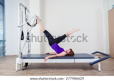 gym woman pilate instructor stretching in reformer bed - stock photo