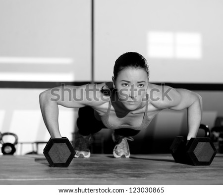 Gym woman push-up strength pushup exercise with dumbbell in a fitness workout - stock photo