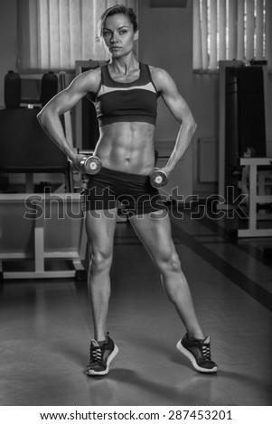 Gym woman push-up strength pushup exercise with dumbbell in a fitness workout. Athletic young woman doing exercises. - stock photo