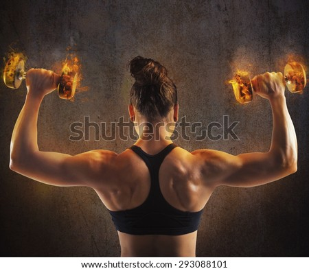Gym woman train back with fiery dumbbells - stock photo
