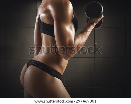 Gym woman train with dumbbell in thong - stock photo