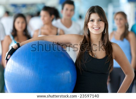 Gym woman with a pilates ball standing in front of a group - stock photo