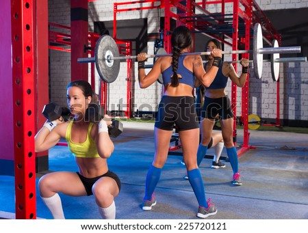 Gym women with barbell lifting and hex dumbbell workout exercise - stock photo
