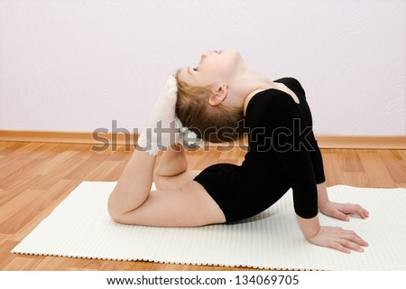 Gymnast cute little girl doing exercises at home - stock photo