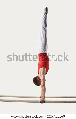 Gymnast Doing Handstand on Parallel Bars - stock photo