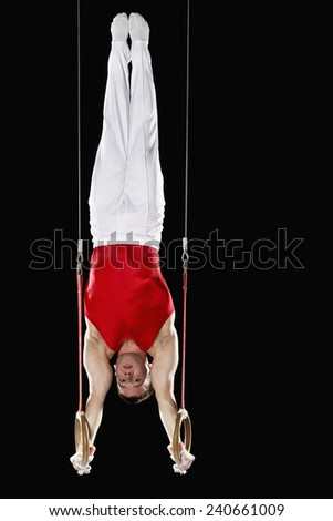 Gymnast Doing Handstand on Stationary Rings - stock photo