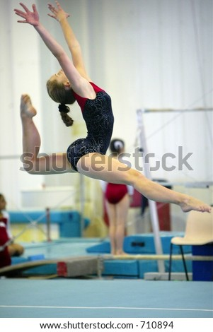 gymnast jumping into the air and performing a split leaping jump while wearing a black and red leotard with a gymnasium background - stock photo