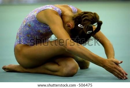 gymnast on floor in the start finish position - stock photo