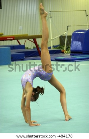 gymnast on floor with leg raised straight in the air - stock photo