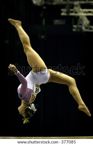 Gymnast performs a backwards walk over on a beam during a competition - stock photo