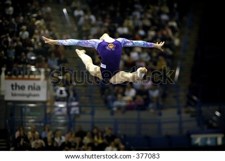 Gymnast performs a split leap on beam during a competition at the NIA Birmingham UK - stock photo
