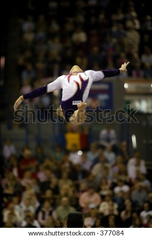 Gymnast performs a split leap on beam during a gymnastics competition - stock photo