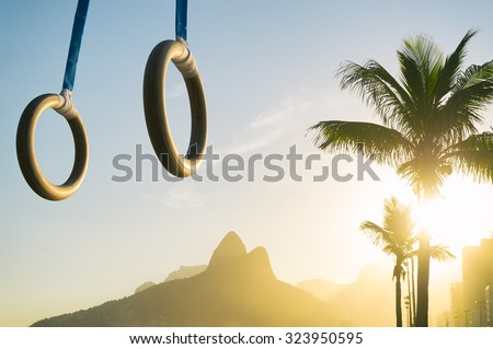 Gymnast rings hanging in golden sunset light above Ipanema Beach at the Rio de Janeiro, Brazil mountain skyline - stock photo