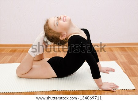 Gymnast smiling little girl doing exercises at home - stock photo