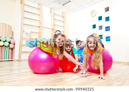 Gymnastic balls and kids on them - stock photo