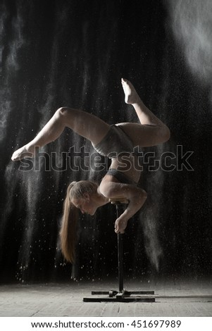 Gymnastic woman handstand on equilibr at sprinkled flour - stock photo
